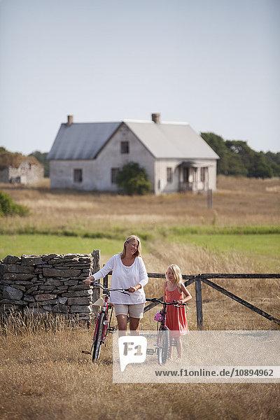 Schweden  Gotland  Faro  Mutter und Tochter (8-9) beim Radfahren auf dem Bauernhof