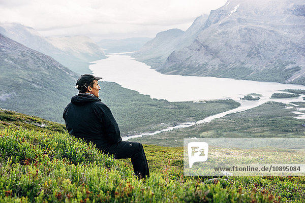 Sweden  Lapland  Kaitumjaure  Kungsleden  Male hiker sitting and looking at river in mountain valley