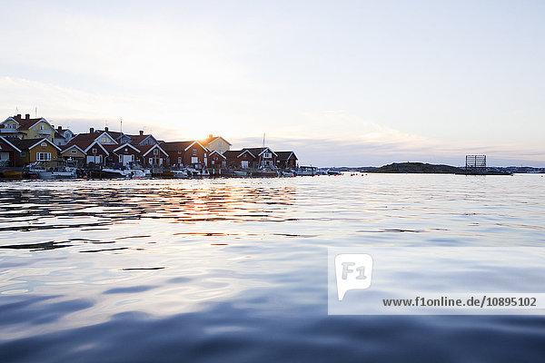 Schweden  Bohuslan  Skafto  Häuser und Motorboote bei Sonnenuntergang