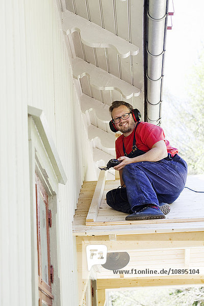 Schweden  Vastra Gotaland  Olofstorp  Porträt des Hausbesitzers auf dem Hausdach