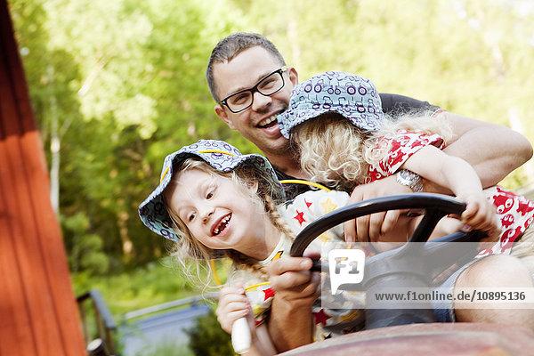 Schweden  Vastra Gotaland  Olofstorp  Vater mit Töchtern (4-5  8-9) beim Traktorfahren