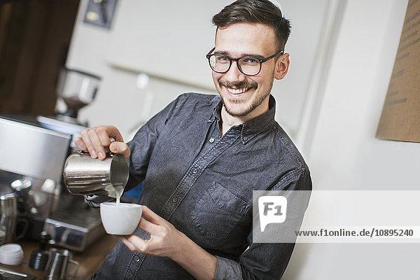 Schweden  Lächelnder Barista macht Latte
