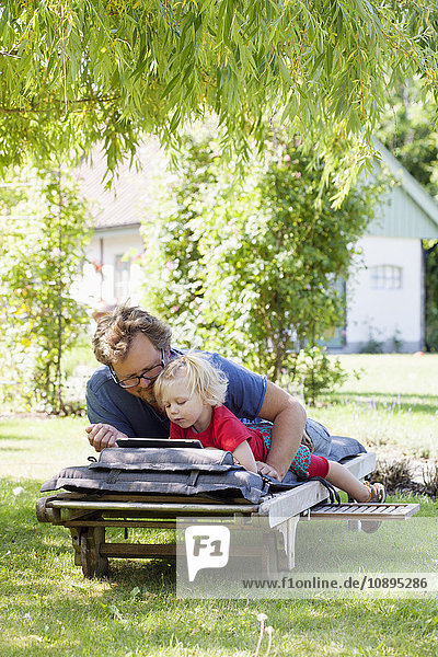 Sweden  Skane  Mossby  Daughter with father lying on deckchair and using tablet pc
