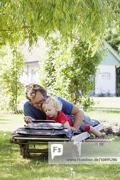 Schweden  Skane  Mossby  Tochter mit Vater auf Liegestuhl liegend und mit Tablet PC