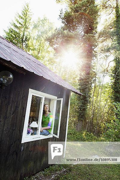 Schweden  Gotland  Frau am offenen Fenster sitzend