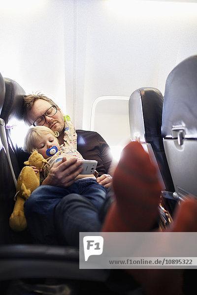 Schweden  Vater und Tochter (2-3) schlafen im Flugzeug