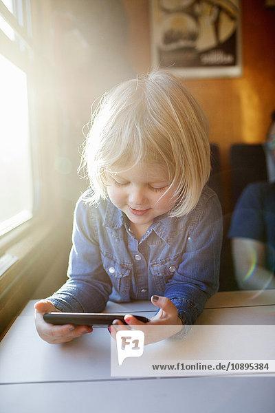 Schweden  Mädchen (2-3) mit Smartphone im Zug