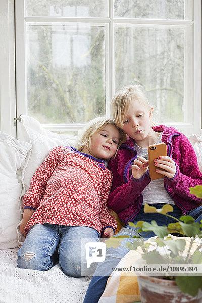 Schweden  Schwestern (4-5  10-11) mit Smartphone zu Hause