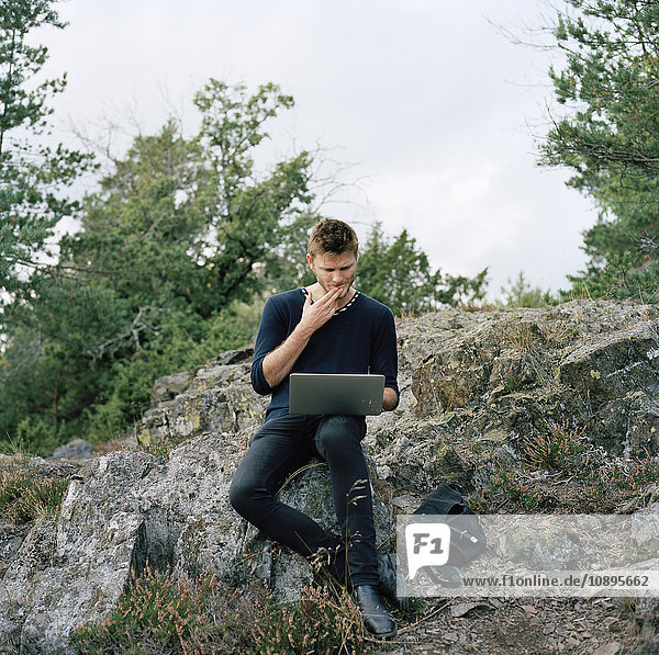 Schweden  Sodermanland  Nacka  Mann mit Laptop im Wald