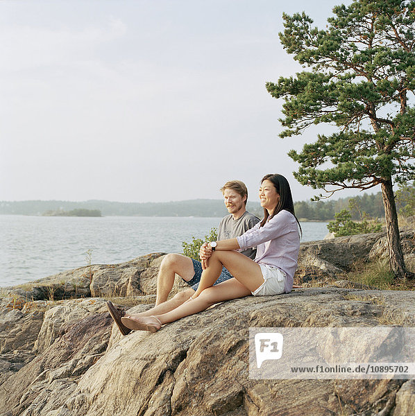 Schweden  Stockholm Archipel  Sodermanland  Nacka  Mittleres erwachsenes Paar auf Felsen sitzend  Blick aufs Meer