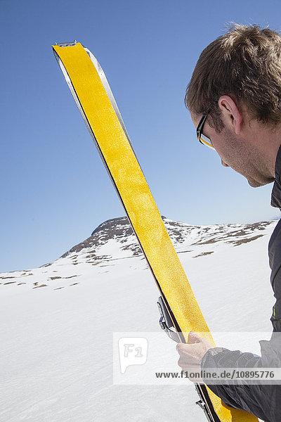 Schweden  Jamtland  Snasahogarna  Mittlerer Erwachsener mit gelbem Ski
