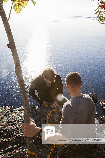Schweden  Medelpad  Sundsvall  Essvik  Brattberget  Zwei Männer binden Kletterseil