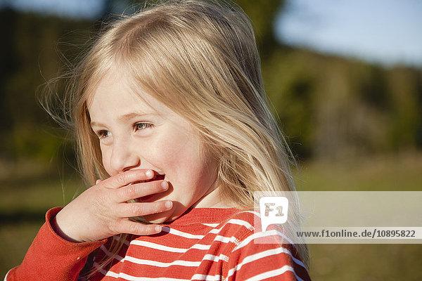 Schweden  Medelpad  Portrait eines blonden Mädchens (2-3)  das den Mund mit der Hand bedeckt.