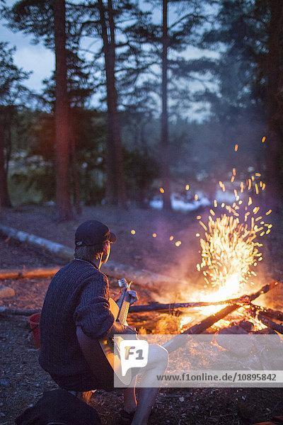 Schweden  Medelpad  Mann spielt Gitarre am Lagerfeuer