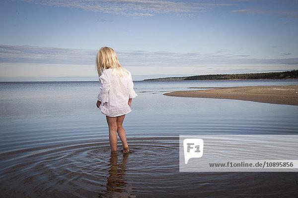 Schweden  Medelpad  Juniskarr  Blondine (6-7) im Wasser watend