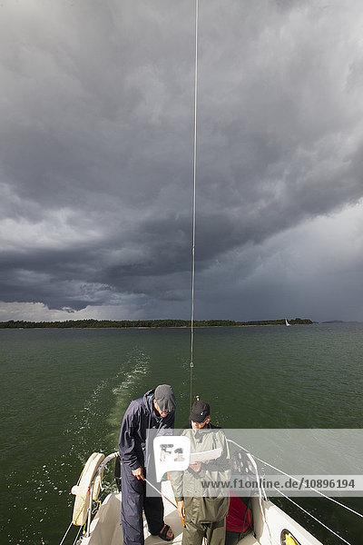 Schweden  Stockholm Archipel  Zwei Männer auf der Karte auf dem Boot
