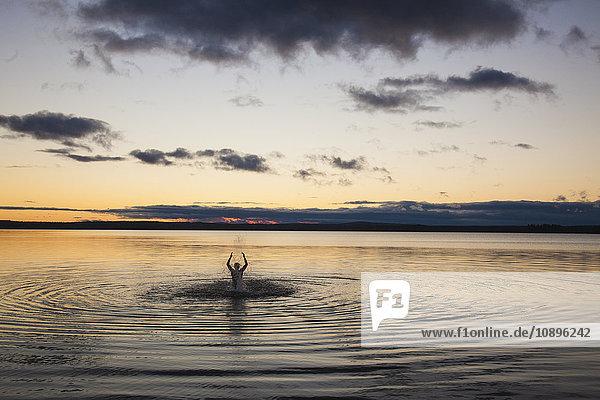 Schweden  Medelpad  Bjorkofjarden  Silhouette des im See schwimmenden Mannes