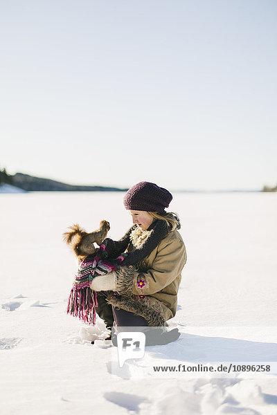Schweden  Medelpad  Sundsvall  Mädchen (6-7) hockend mit Eichhörnchen am Knie