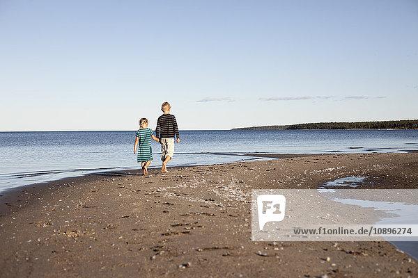 Schweden  Medelpad  Bergafjarden  Bruder (10-11) mit Schwester (6-7) zu Fuß entlang der Ostseeküste