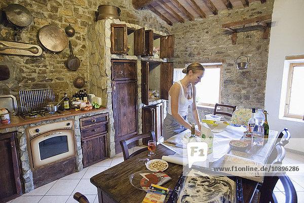 Italien  Toskana  Frau bei der Zubereitung von Speisen in der Küche