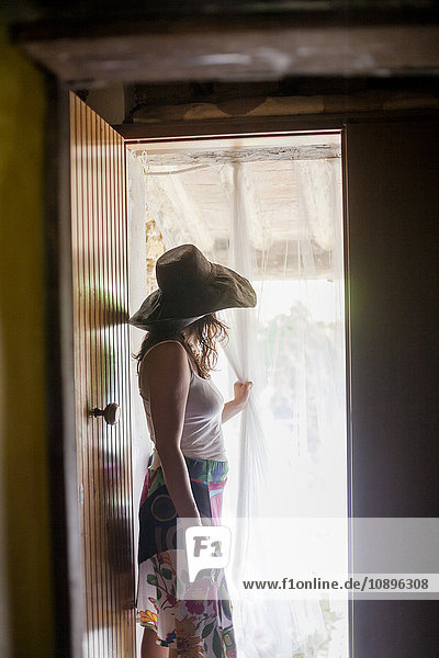 Italien  Toskana  Frau in Sonnenhut mit Blick durch den Türvorhang