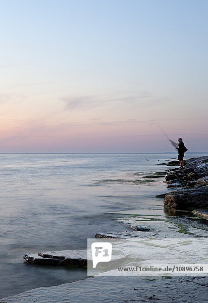 Schweden  Oland  Sandvik  Mann fischen bei Sonnenuntergang