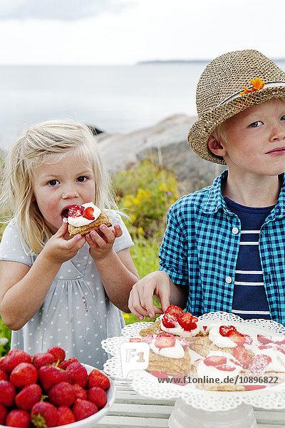 Schweden  Uppland  Roslagen  Kinder (6-7  8-9) essen Erdbeer-Dessert im Freien