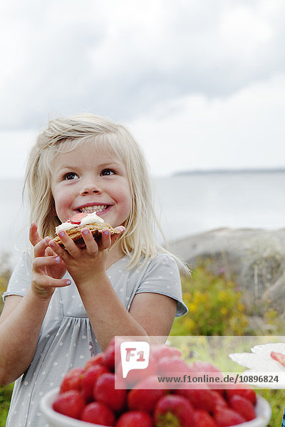 Schweden  Uppland  Roslagen  Girl (6-7) essen Erdbeer-Dessert im Freien