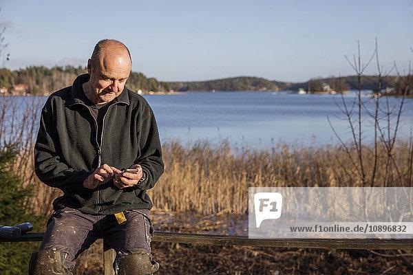 Schweden  Uppland  Rindo  Mann auf Bank sitzend und mit Smartphone