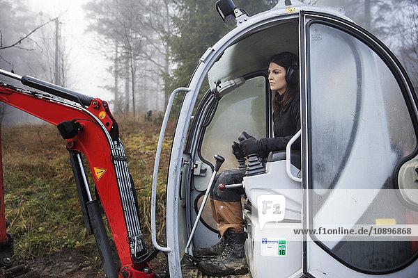 Schweden  Uppland  Nacka  Frau beim Bulldozerfahren im Wald