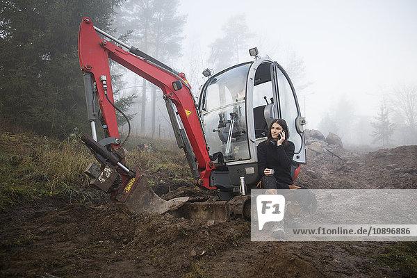 Schweden  Uppland  Nacka  Frau sitzend bei Bulldozer und per Telefon