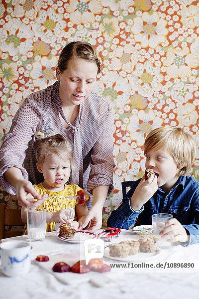 Schweden  Junge (10-11) und Mädchen (2-3) beim Kuchenessen