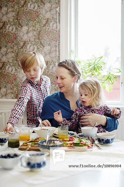 Schweden  Mutter mit zwei Kindern (2-3  10-11) beim Frühstücken