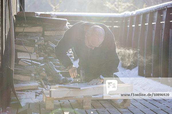 Schweden  Uppland  Mann schneidet Holz mit Stichsäge
