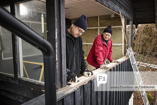Schweden  Uppland  Rindo  Männer bauen Holzgeländer