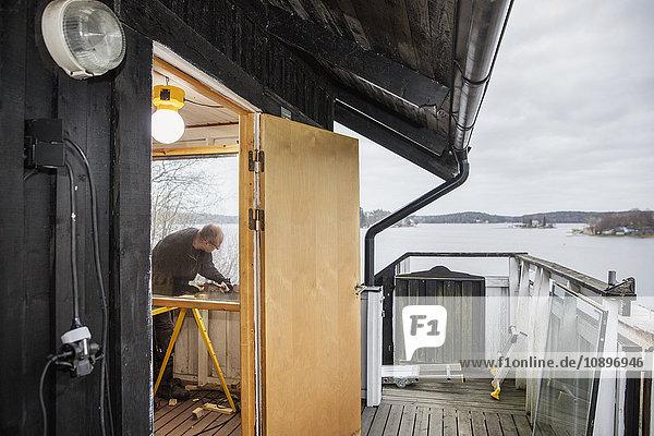 Schweden  Uppland  Stockholm Archipel  Rindo  Mann baut Holzgeländer