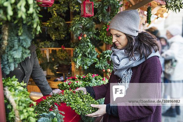 Schweden  Stockholm  Gamla Stan  Frau wählt Weihnachtskranz am Markt