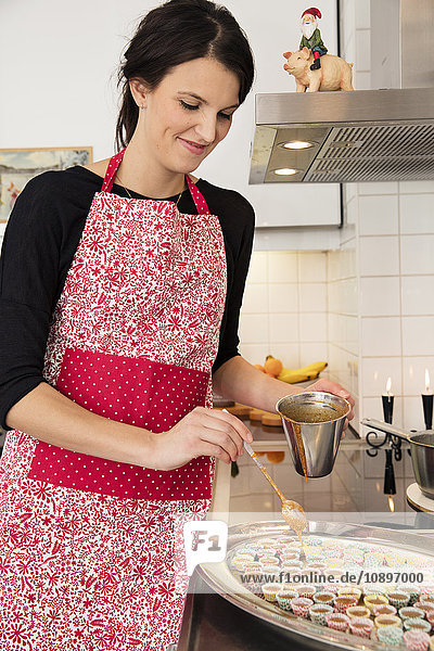 Schweden  Frau gießt Kuchenmasse in Muffinbehälter
