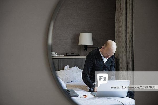 Japan  Tokio  Shibuya  Mann auf dem Bett sitzend und mit Laptop