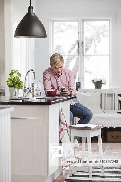 Schweden  Teenage boy (16-17) texting in der Küche