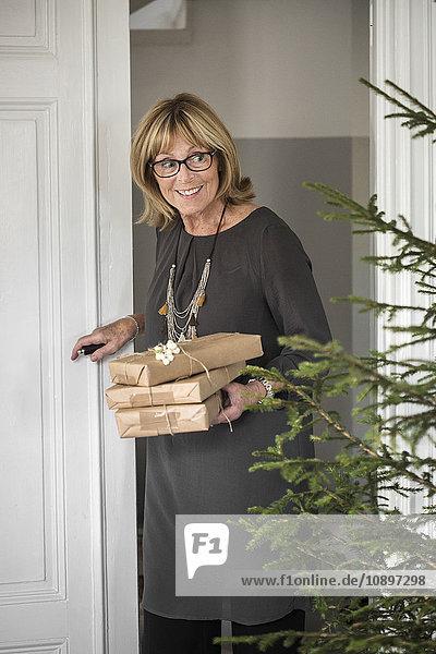 Schweden  Lächelnde Seniorin betritt Zimmer mit Weihnachtsgeschenken