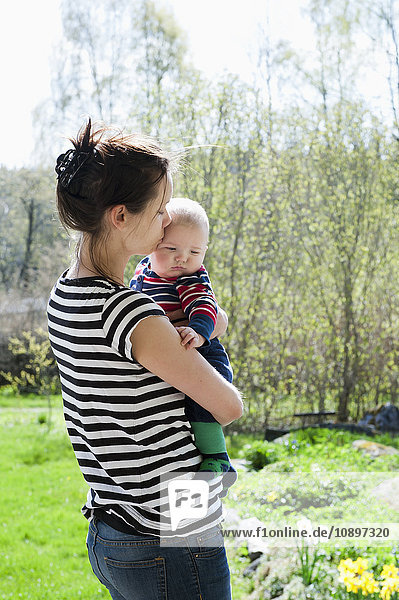 Sweden  Ostergotland  Vikbolandet  Woman carrying and kissing baby boy (6-11 months)