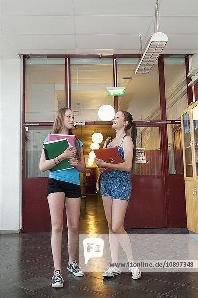 Zwei Mädchen (14-15)  die in der Schule stehen und reden.