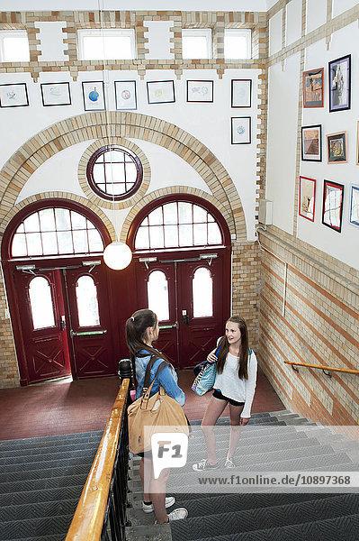 Zwei Mädchen (14-15) auf der Treppe stehend  sprechend
