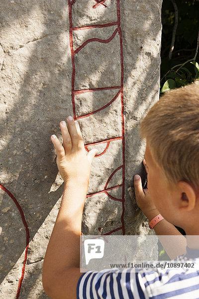 Schweden  Oland  Boy (10-11) berührende Wand