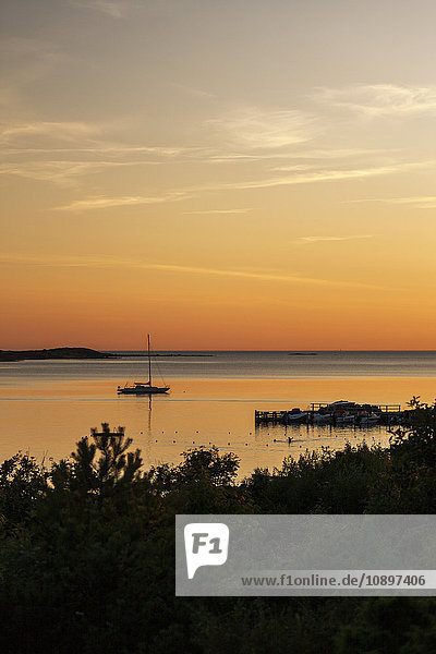 Schweden  Halland  Varberg  Tangaberg  Segelboot liegt bei Sonnenuntergang in Ufernähe.