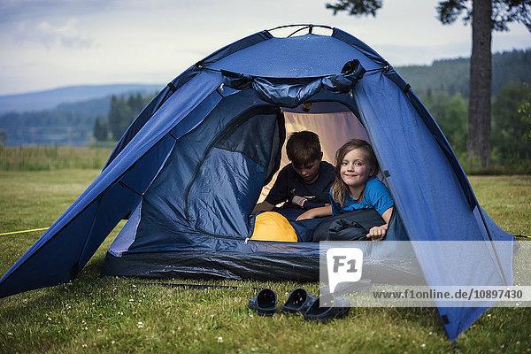 Schweden  Dalarna  Salen  Kinder (8-9  10-11) im Zelt auf der Wiese