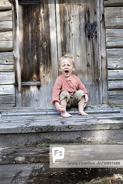 Schweden  Harjedalen  Ytterberg  Junge (2-3) vor der Hütte sitzend