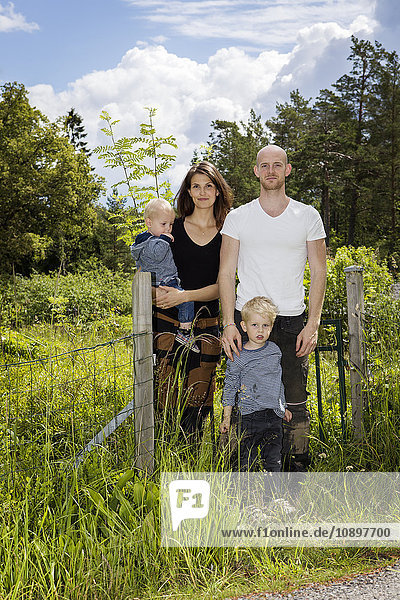 Schweden  Stockholm  Uppland  Nacka  Familie mit zwei Kindern (18-23 Monate  4-5) inmitten von üppigem Laub.