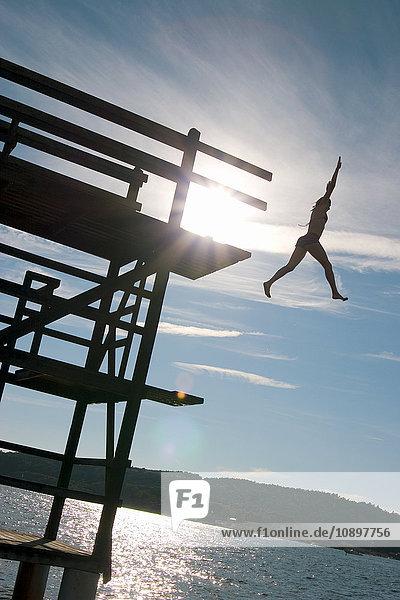 Schweden  Bohuslan  Fjallbacka  Silhouette der Frau  die von der Plattform springt